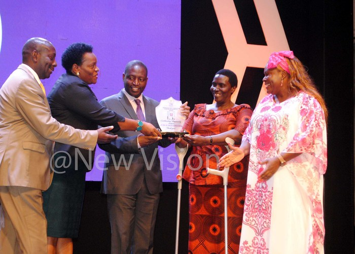 enensio umuramye eace utuuzo avid ahati the inister of tate for inance and ellen samo receiving an award from osa alango nited ation esident oordinator on behalf of ebecca adaga as the est utstanding ersonalityhis was during the gender and equity responsive planning and budgeting awards 2019 at mperial oyale otel on ctober 30 2019 hotos by ary ansiime