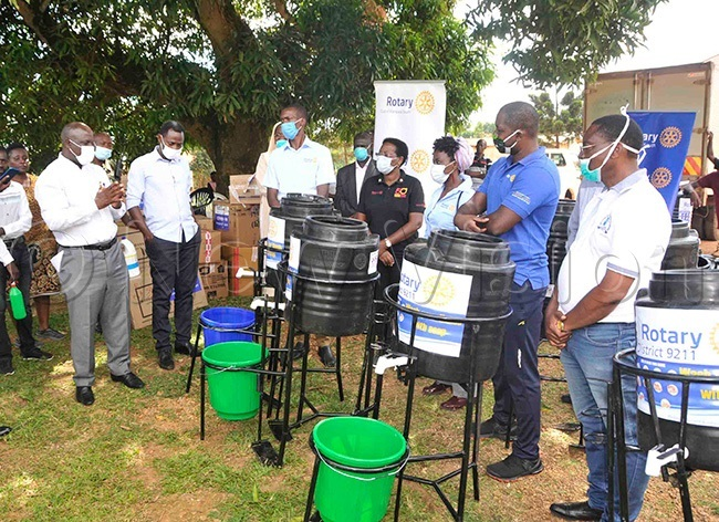 amwine and the 19 taskforce members receiving a donation including hand washing equipment thermometer guns sanitizers medical gowns and gloves among others from the otary lub of ampala outh and otary lub of ukono