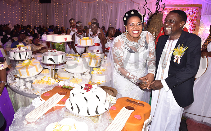 abirye and sebulime cutting cake at the wedding