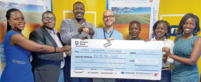 gandas orporate communications manager alery kecho 3rd eft receives a sh50m cheque from pedag nterfreight eneral anager ino chmitz middle ooking on left to right almah uwule ommercial anager  pedag nterfreight ganda imited ohn irungi abirukamu igital   ganda eotina amirembe ead mports acheal uyiga ustomer elations and obusingye
