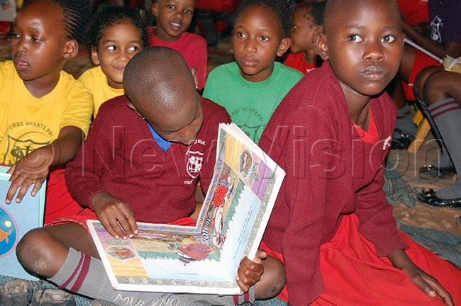 pupil of amirembe nfant rimary chool reading a story book