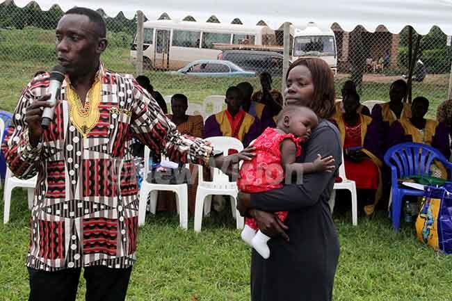 rig en am mara the deputy hief of ilitary ntelligence introducing the child who survived the accident to mourners during the funeral of its mother in ole on riday hoto by udson punyo