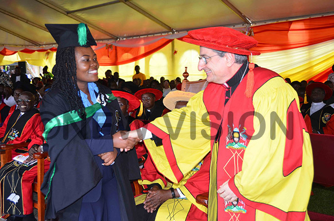 rchbishop uigi ianco who was the uest of onour shares a light moment with one of the graduands