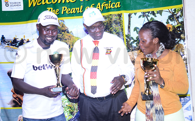 est ile olf lubs oses ebi left and ntebbe lubs iana abukenya right pose with ganda ourism deputy  radford chieng after he handed them their trophies hoto by ichael subuga