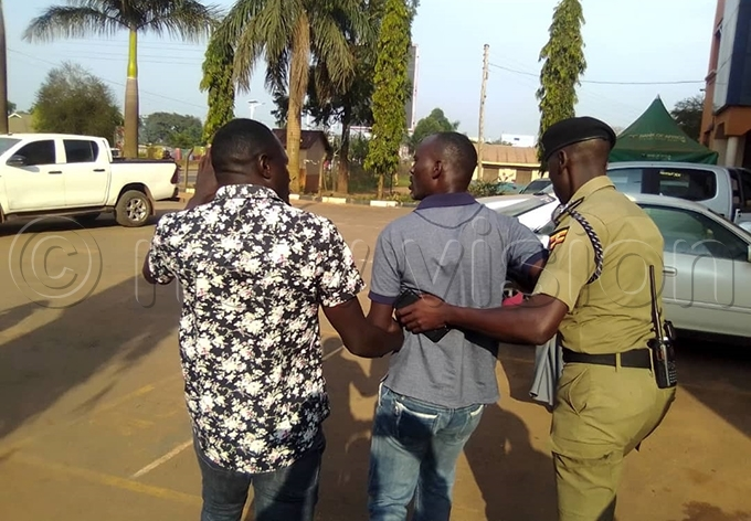 ne of the councillors is led away by a olice officer hoto by bu atuusa