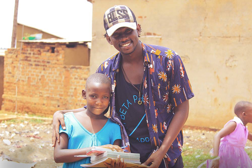 evixone hands over books to a school child