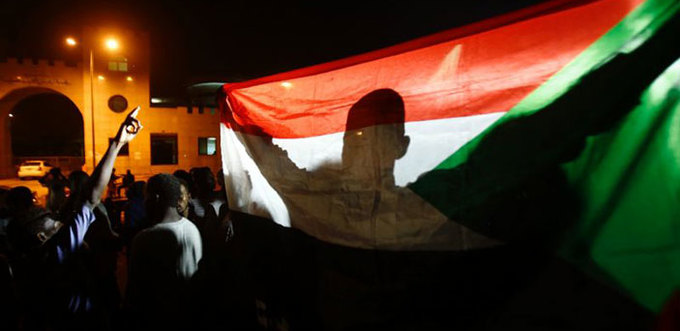 man holds the udanese flag during a nighttime demonstration outside the army headquarters in hartoum on ay 30 2019  hoto