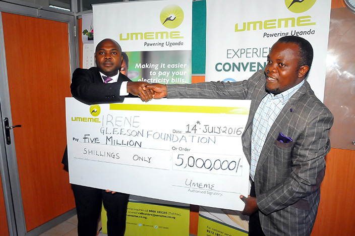 anaging irector of meme  ganda  elestino  alungi  hands over a dummy cheque of sh5m to ev atrick semambo of leeson oundation  to buy books for pupils in amwo and itgum districts which performed poorly in last years  his was on  uly 142016 2016hotos ilfred anya