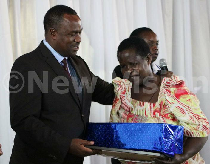 octor lioda umwesigye left hands a present to ita amirimu one of the pioneer volunteers of each ut buya