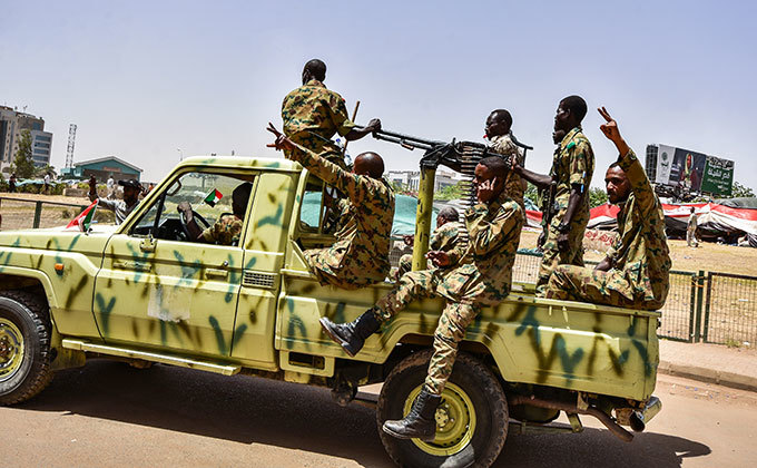 udanese soldiers flash the victory gesture as they sit in the back of a technical pickup truck mounted with a turret nearby a scene of gathering demonstrators during a rally demanding a civilian body to lead the transition to democracy outside the army headquarters in the udanese capital hartoum on pril 13 2019  hoto by