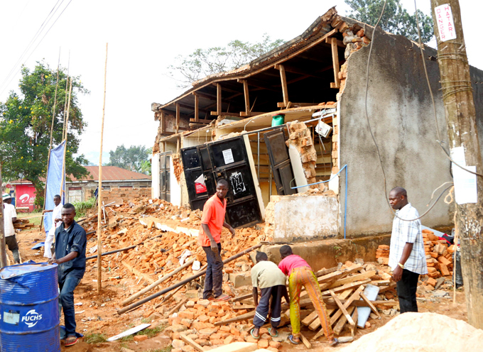 eople remove wreckage of a house damaged following the earthquake  hoto