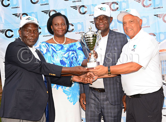 eniors golf open champion lex outhino right receives the winners trophy from eniors chairman ark tege left as   oard ember live umonya and  irector eneral rof avid panga look on after the eniors pen tournament at itante ec 1 2019