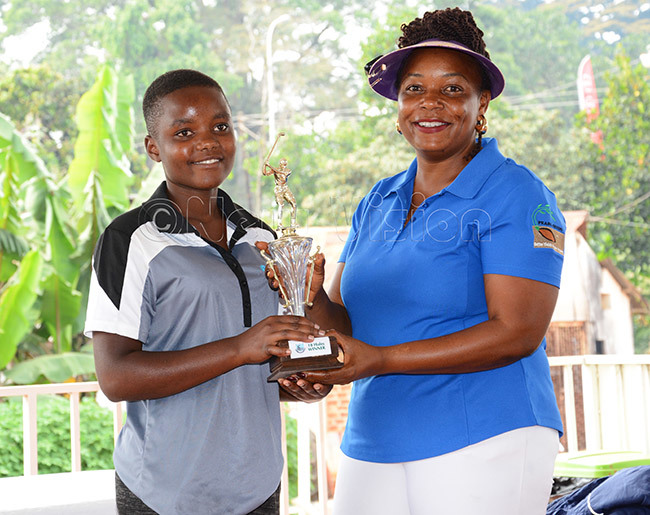 president va agala right presents the overall winners trophy to the girls category winner ilka inembabazi after the ntebbe uniors pen at ntebbe lub