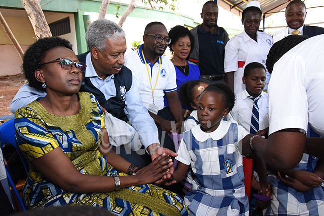 inister of ealth r ane cheng looking on as her daughter gets immunized at reen ill cademy on hursday hoto by palanyi sentongo