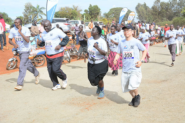 ome of the articipants in the 5km run in action alongside apan eputy ead of ission orri izumoto right during the eamganda okyo 2020 run at the oma round in apchorwa