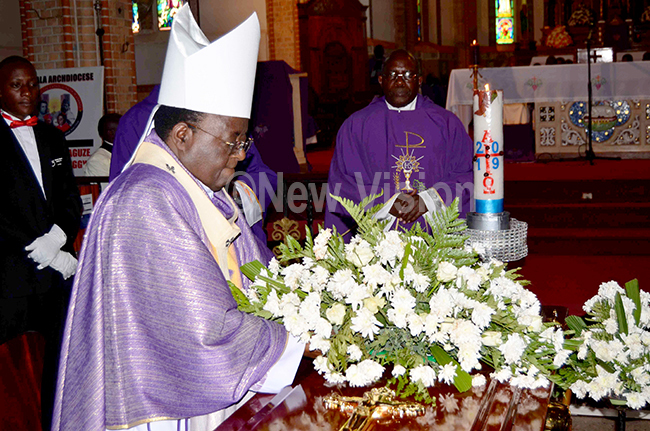 rchbishop yprian izito wanga laying a wreath on the casket bearing the remains of  eacon ndrew rian ayega during the funeral mass at ubaga athedral on onday ugust 5 hoto by athias azinga