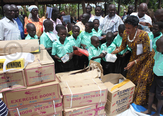 gabiirwe and the  chairperson of asindi district ilson ugimba handing over scholastic materials to children hoto by bou isige