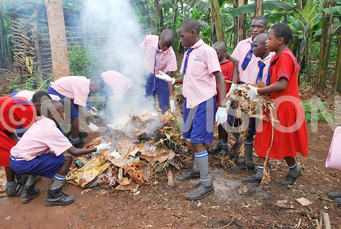 upils of ighfield rimary chool in ayaza ampala burning rubbish during a community sensitisation exercise on sanitation in the area in une 2014