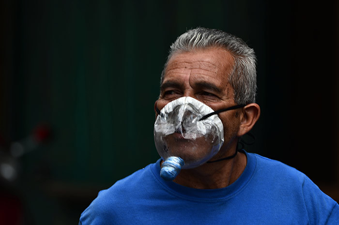man wears a makeshift face mask made from a plastic bottle against the spread of the new coronavirus as he walks along an avenue in downtown in egucigalpa on arch 22 2020  uthorities have confirmed 26 cases of 19 in the country so far hoto by