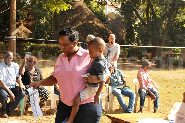 voter looks at a  ballot paper before casting her vote  at the ational heatre polling station