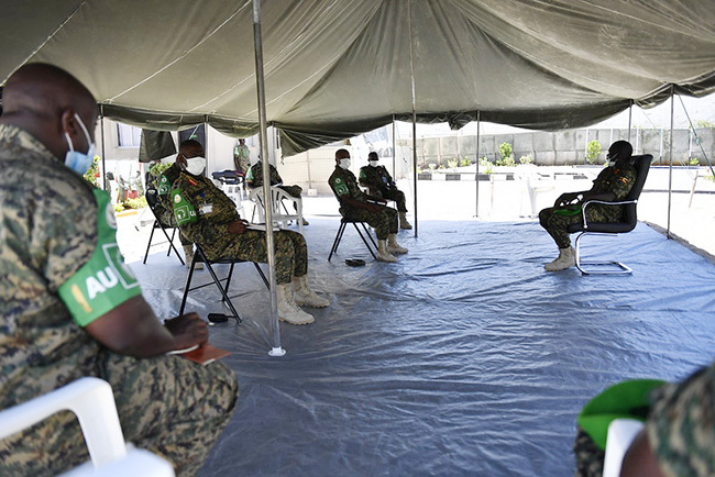 gandan soldiers serving under the frican nion ission in omalia  hold a meeting at the ector ne eadquarters in ogadishu omalia while maintaining social distance