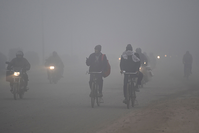 ommuters ride bikes and bicycles along a road amidst heavy fog in aridabad on uesday morning  hoto