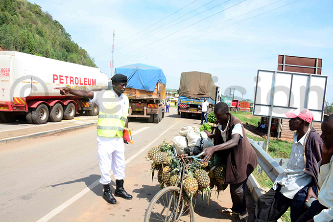 gandan traffic officer directs a pineapple vendor away from the parking yard for trucks at irama ills hoto by ddie sejjoba