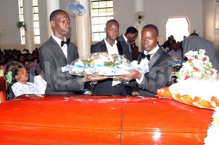 hildren of the late director of ampala quality primary school dward asisiri ayemba lan irabo lex  enneth ark gaba laying a wreath on his casket during the funeral service at ll aints athedral ampala hoto by ichard anya