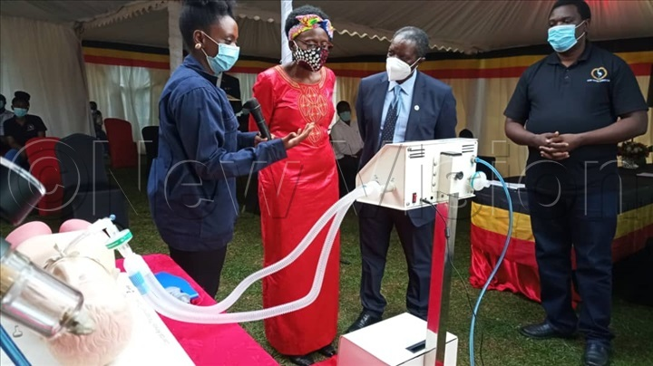 Pauline Korukundo the vehicle Integration Manager at KMC demonstrates to the Minister of Health how the how the medical ventilator works.
