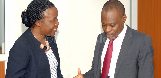 and probe commission deputy lead counsel ohn osco uuza right interacts with ank of ganda legal counsel argret aggwa at the land probe inquiry on ednesday hoto by enis ibele