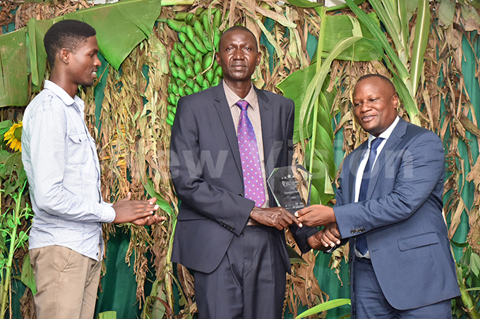 s  athias atambaright hands incent jok his award as son eonard dongo looks on