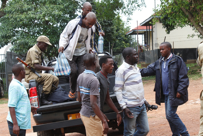 he suspects disembarking from olice trucks ahead of their court appearance hoto by ulius uwemba