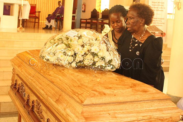 he widow lice ego lays a wreath on the casket of his late husband at t harles wanga atholic hurch tinda anuary 23 2020 hotos by atricia uryahebwa