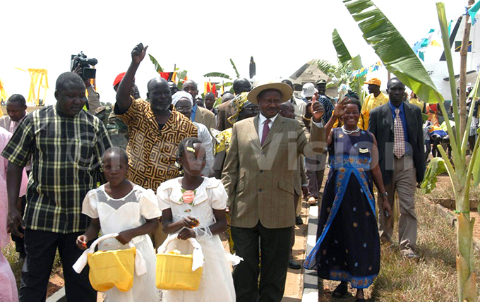 resident oweri useveni  and ormer udans irst ice resident ate ol ohn arang wave to the public on arrival at ulu nternational irport on anuary 272005