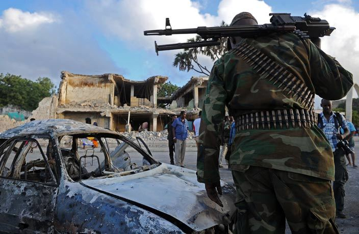 omali soldiers and resident stand near wreckage car and buildings on ebruary 27 2016 in ogadishu omalia t least 14 people were killed on ebruary 26 as twin blasts and gunfire rocked a hotel and neighbouring park in central ogadishu police said in an attack claimed by the laedalinked hebab militants