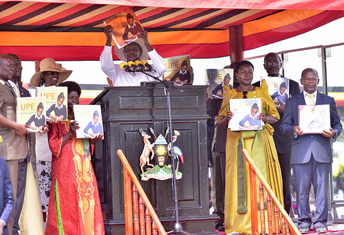 resident oweri useveni hold aloft a book celebrating 20 years of niversal rimary ducation   hoto