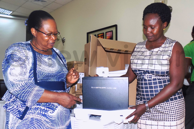 astha ibirige  handing over a computer to lorence amimbi the  prevention coordinator at the nfectious isease nstitute during the launch of  hoto by audha akandha