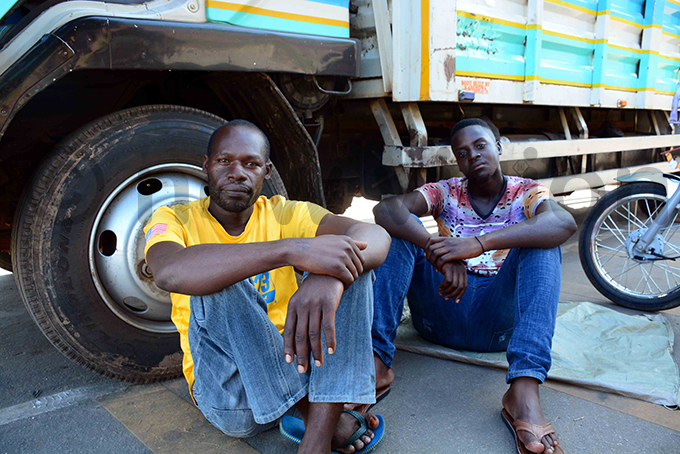 ruck drivers sit beside their trucks at irama ills hoto by ddie sejjoba