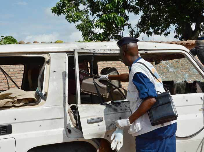 urundian security official gathers evidence from the bloodstained and shrapnelriddled vehicle in which utsi eneral and security advisor to urundis vice president thanase araruza was killed along with his wife and daughter in an attack by heavilyarmed men on pril 25 2016 in ujumbura