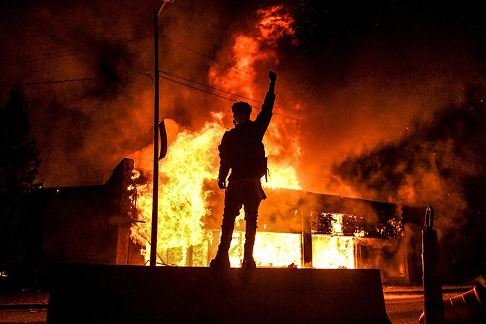 protester reacts standing in front of a burning building set on fire during a demonstration in inneapolis innesota on ay 29 2020 over the death of eorge loyd a black man who died after a white policeman kneeled on his neck for several minutes hoto by handan