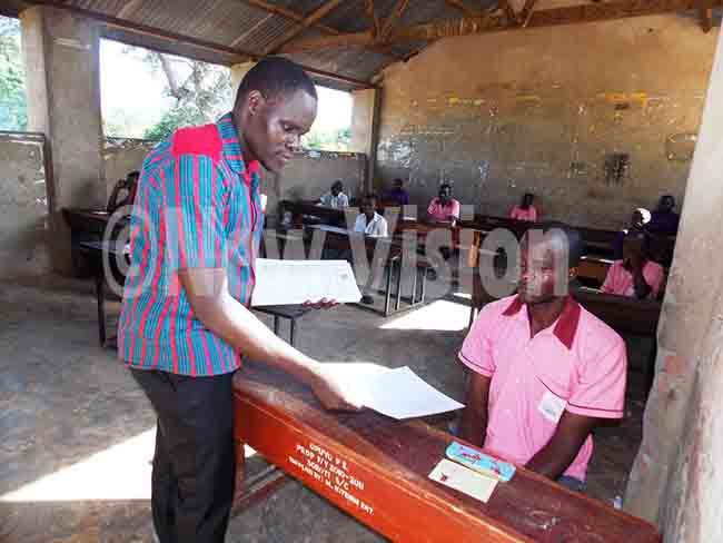invigilator ames wayu giving a  question paper to imon kwii at puyo rimary chool in oroti kwii said he wants to become an engineer hoto by mmanuel lomu