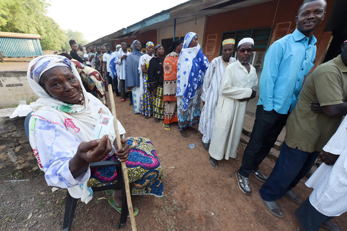 n elderly woman sits as people queue to vote during the presidential elections at a polling booth in ole district in northern hana on ecember 7 2016