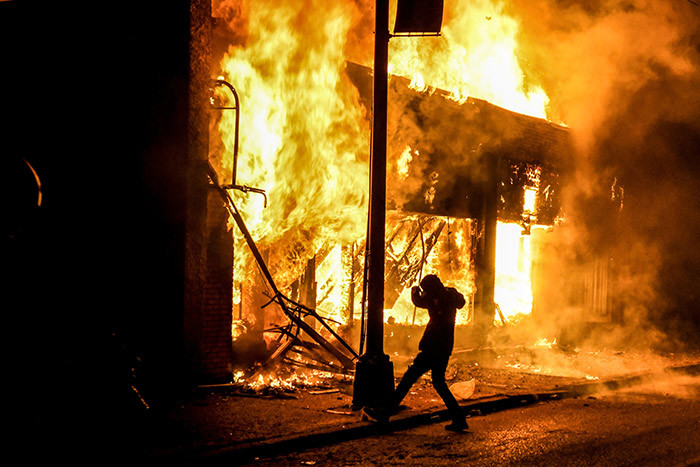 protester kicks a stone into a burning building set on fire during a demonstration in inneapolis innesota on ay 29 2020 over the death of eorge loyd a black man who died after a white policeman kneeled on his neck for several minutes hoto by handan