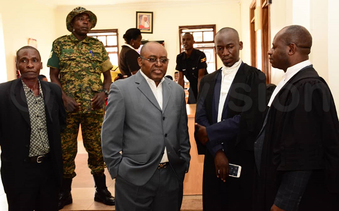 umbere confers with members of his legal team at the court in ololo hoto by imothy urungi