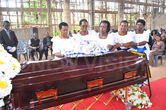 itah itandwe left being helped by her relatives to lay a wreath on the casket of her late husband