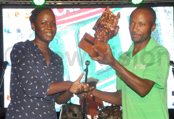 astle ite brand manager ulian sentamu  presents a trophy to professional incent yamukama after the tournament hoto by ichael subuga