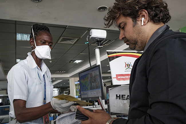 n airport health worker checks travel documents of passengers