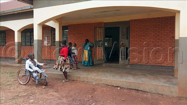 child with special needs ames addu waits to be helped to enter a hall as there are no tramps for easy access at acred eart inja aroli rimary chool in akiso district on aturday ovember 23 2019