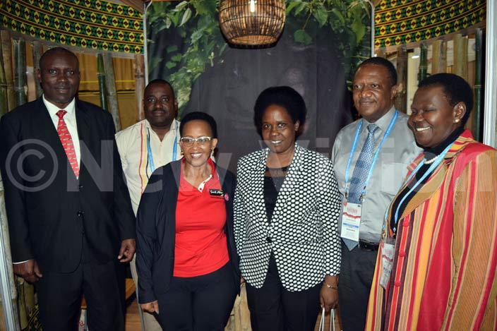 outh frican eputy inster of ourism okozile asa with representatives of gandas inistry of ourism and  during her visit to the gandan stall