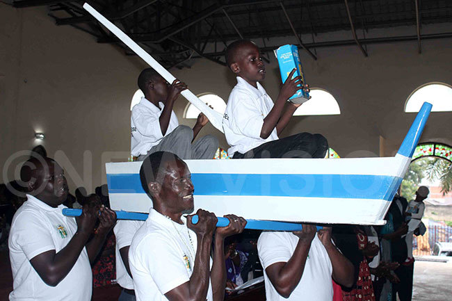 hristians from oroti atholic diocese carrying two boys who presented the oly ook in an improvisedsymbolic boat during the sendoff function for the ishopelect of oroti sgr oseph ciru at t onzaga onza atholic hurch ireka on unday ay 19